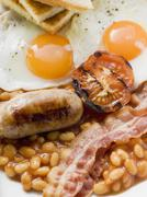 Stock Photo of Baked beans, sausage, bacon, tomato, fried eggs and toast