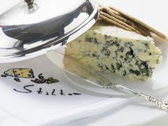 Wedge of Stilton with crackers and cheese knife - stock photo