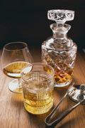 Cognac & whisky in glasses & carafe, ice tongs beside them - stock photo