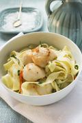 Ribbon pasta with fried scallops - stock photo