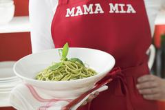 Woman in red apron holding plate of spaghetti with pesto - stock photo