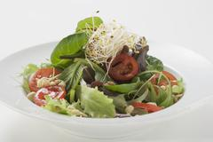 Stock Photo of Salad leaves with sprouts, tomatoes and pine nuts