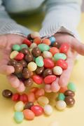 Child's hands holding coloured sugar eggs - stock photo