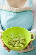 Woman holding small colander containing green gooseberries - stock photo