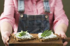 Person holding wholemeal bread with quark & ramsons on board Stock Photos
