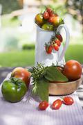Various types of tomatoes on table out of doors - stock photo