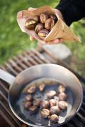 Hand holding roasted chestnuts in paper bag Stock Photos