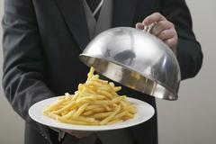Butler lifting serving dome from plate of chips - stock photo