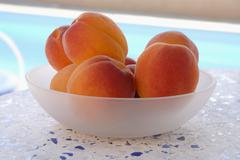 Stock Photo of Apricots in a bowl by a pool