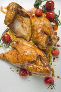 Roast chicken, jointed, with cherry tomatoes - stock photo