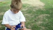 Child busy playing on cell phone in grass Stock Footage