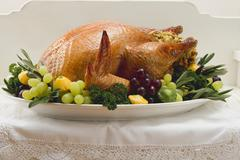 Stuffed turkey with herbs, grapes and patty pan squashes - stock photo