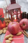 Christmas decoration with apples, nuts, cinnamon & lantern Stock Photos