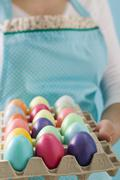 Woman holding egg tray full of coloured Easter eggs Stock Photos