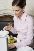 Woman eating salad while working on laptop in restaurant Stock Photos