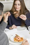 Man offering woman fried prawn in restaurant Stock Photos