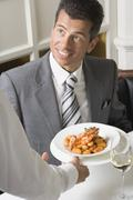Waiter serving gnocchi with prawns to man - stock photo