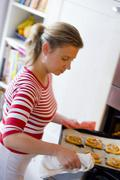 Woman putting tray of tomato tarts into the oven - stock photo