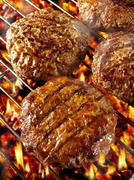 Burgers on barbecue rack Stock Photos