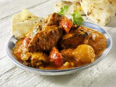 Jalfrezi (spicy meat curry, India), with flatbread - stock photo