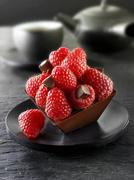 Stock Photo of Small chocolate cake with raspberries to serve with tea