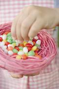 Child's hands holding Easter nest full of coloured sugar eggs - stock photo