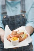 Woman holding tiger prawns with dip on napkin Stock Photos