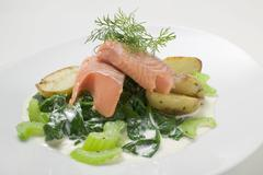 Salmon trout fillet with spinach, celery and potatoes - stock photo
