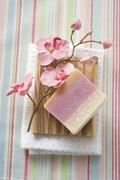 Soap and flowers on wooden soap dish on towel Stock Photos