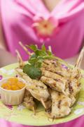 Woman holding plate of satay and chutney - stock photo