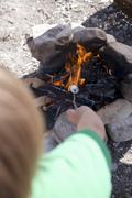 Child grilling marshmallows over camp-fire - stock photo