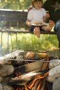Apples on grill rack over camp-fire, child in background - stock photo