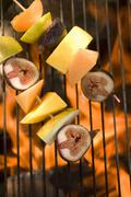Fruit kebabs on barbecue grill rack - stock photo