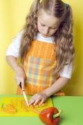 Girl cutting up carrots - stock photo