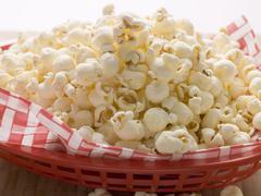 Popcorn on napkin in red plastic basket Stock Photos