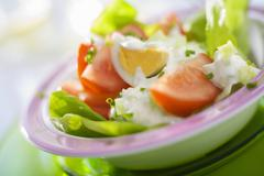Lettuce, egg, tomato and yoghurt dressing Stock Photos