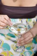 Woman holding green olive on cocktail stick in Martini glass Stock Photos