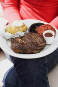 Woman holding plate of steak, baked potato, vegetables & sauce Stock Photos