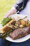 Woman holding plate of steak, grilled vegetables & corn on the cob - stock photo