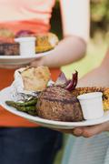 Two women holding plates of grilled steak & accompaniments Stock Photos