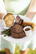 Woman holding a plate of grilled steak and accompaniments Stock Photos