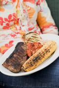 Stock Photo of Woman holding a plate of grilled steak and accompaniments