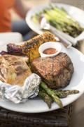 Grilled beef steak with baked potato, corn on the cob, asparagus Stock Photos