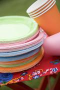 Coloured paper cups and plates on folding stool in garden - stock photo