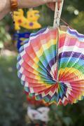 Hand hanging coloured Chinese lantern on washing line in garden - stock photo
