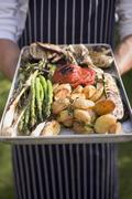 Man holding aluminium tray of grilled vegetables - stock photo