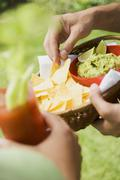 Hands holding basket of guacamole & chips and tomato drink - stock photo