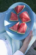 Woman holding a plate of watermelon wedges - stock photo