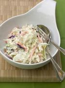 Coleslaw (cabbage salad, USA) in white bowl with cutlery Stock Photos