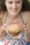 Woman holding hamburger Stock Photos